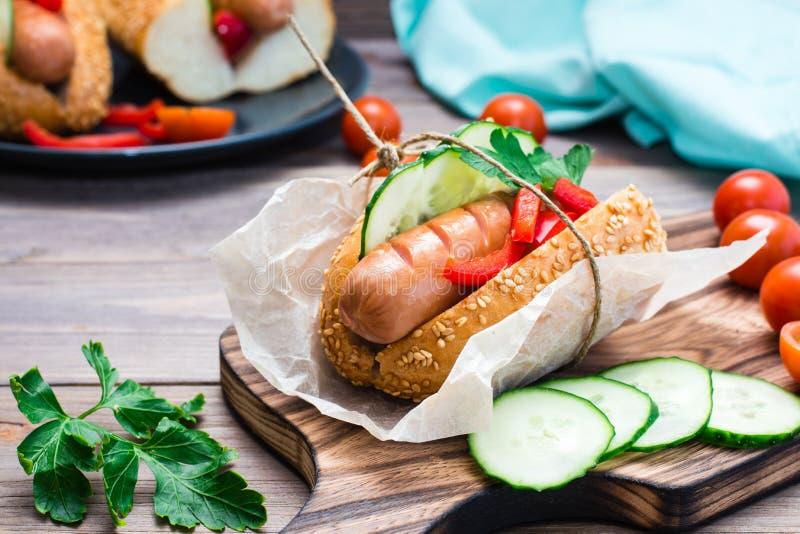 Hot dog appetitoso pronto da mangiare fatto dalla salsiccia, dai rotoli fritti e dagli ortaggi freschi, avvolti in carta pergamen fotografia stock libera da diritti