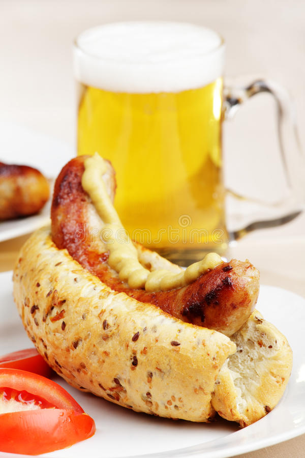 Hot dog and beer. Hot dog with mustard and beer royalty free stock image
