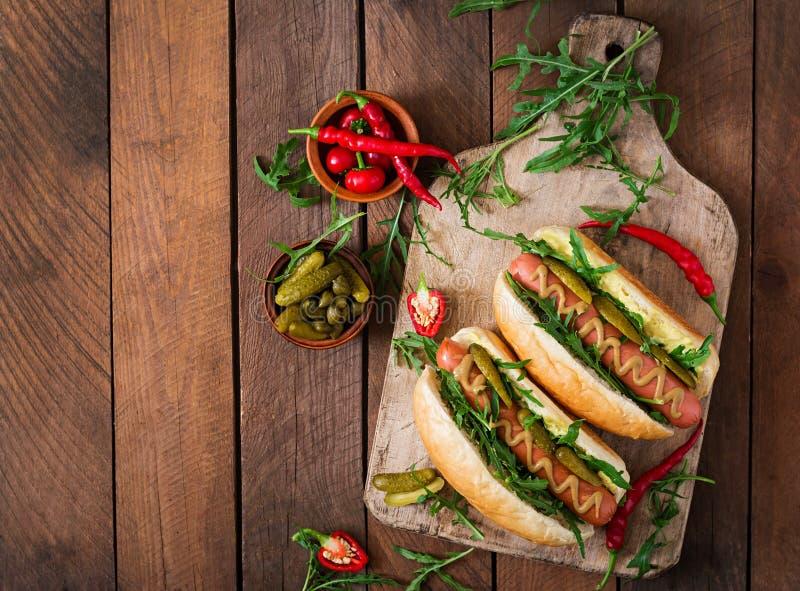 Hot dog con i sottaceti, i capperi e la rucola fotografie stock libere da diritti