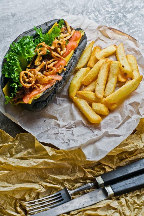 Hot dog con la salsiccia del manzo e le cipolle caramellate in un panino nero Fondo grigio, vista laterale fotografie stock libere da diritti