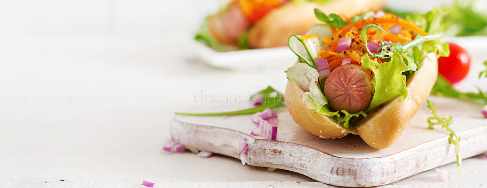 Hot dog with cucumber, carrot, tomato and lettuce on wooden background. Fast food menu. Banner royalty free stock image