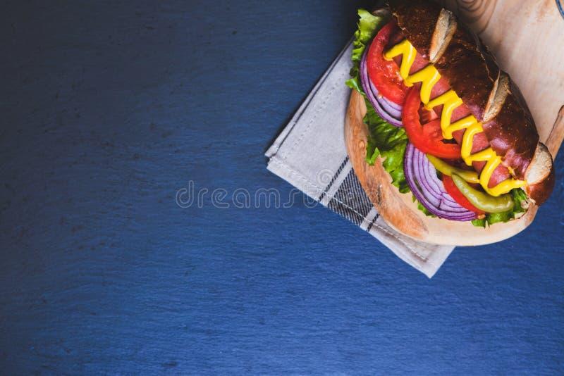 Hot-dog délicieux avec des écrimages sur le fond en bois foncé photo stock