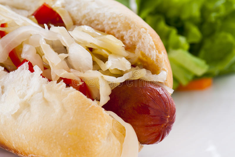 Hot Dog. Grilled Hot Dog with sauerkraut and hot red peppers, with side salad stock photography