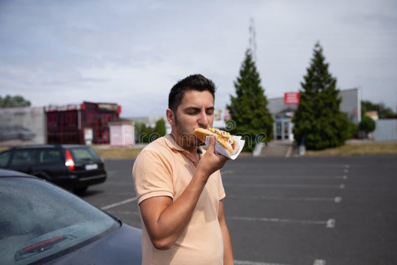 Hot-dog mangeur d'hommes de brune dans le stationnement photos stock
