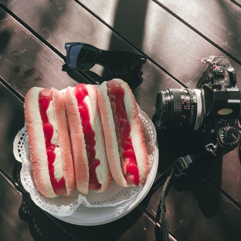 Hot dog na półkowi pobliscy okulary przeciwsłoneczni i kamera zdjęcie royalty free