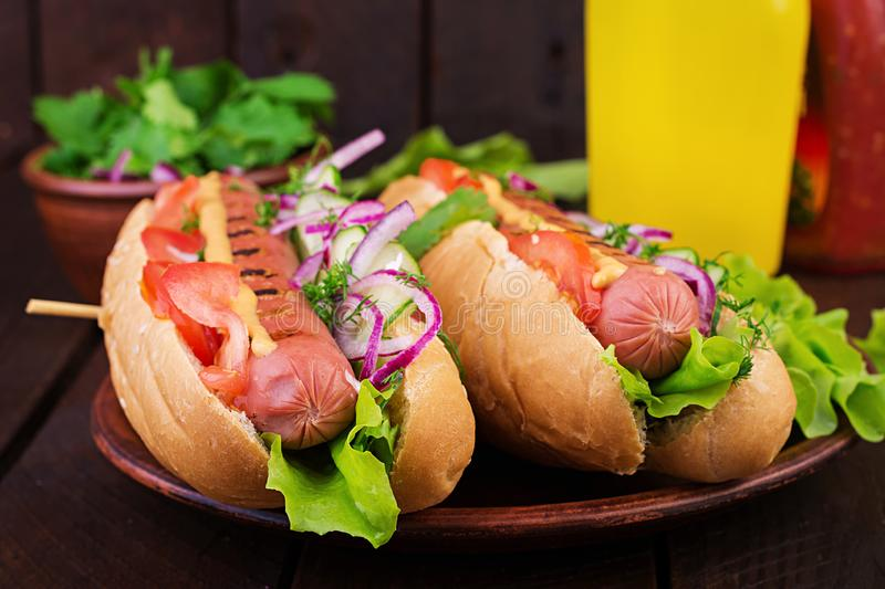 Hot dog with sausage, cucumber, tomato and lettuce on dark wooden background. Hot dog with  sausage, cucumber, tomato and lettuce on dark wooden background royalty free stock photography