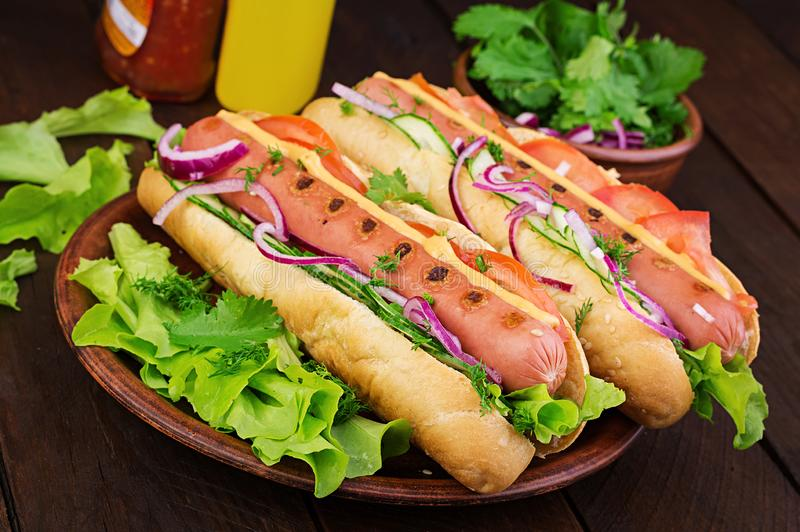 Hot dog with sausage, cucumber, tomato and lettuce on dark wooden background. Hot dog with  sausage, cucumber, tomato and lettuce on dark wooden background stock images
