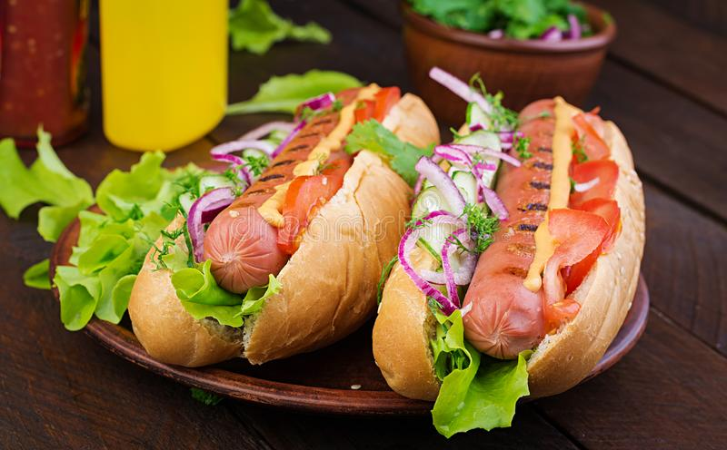 Hot dog with sausage, cucumber, tomato and lettuce on dark wooden stock images