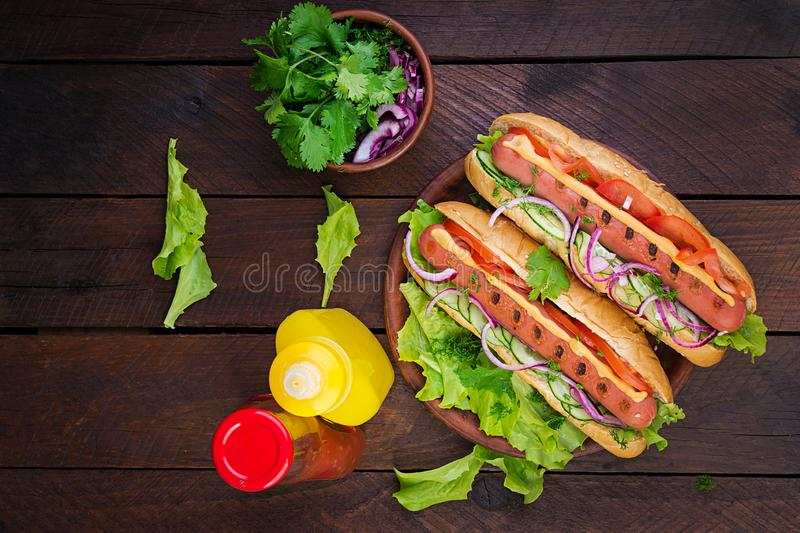 Hot dog with sausage, cucumber, tomato and lettuce on dark wooden background. royalty free stock photos