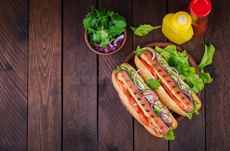 Hot dog with  sausage, cucumber, tomato and lettuce on dark wooden background. royalty free stock photo
