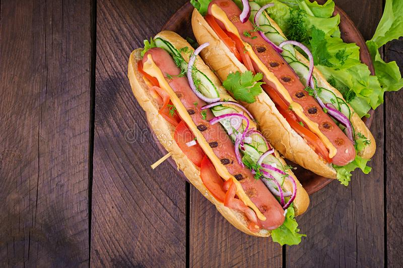Hot dog with sausage, cucumber, tomato and lettuce on dark wooden background. royalty free stock images