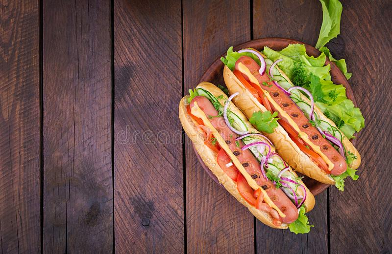 Hot dog with  sausage, cucumber, tomato and lettuce on dark wooden background. Summer hotdog. Top view royalty free stock image