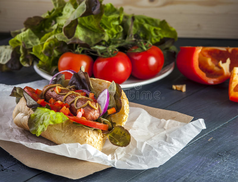 Hot dog with sausage, tomato, onion and mustard. On wooden table. Selective focus royalty free stock image