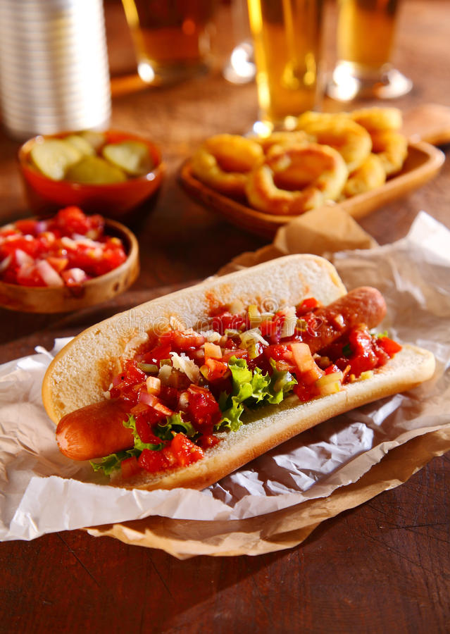 Hot dog topped with fresh vegetable relish. Hot dog topped with spicy fresh vegetable relish with tomato, onion, chili, and lettuce on a smoked Wiener sausage in royalty free stock photo