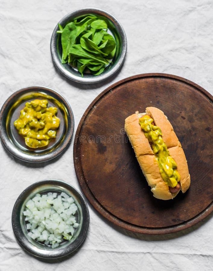 Hot dog tradizionale con il condimento della senape e del cetriolino contro fondo bianco immagini stock libere da diritti