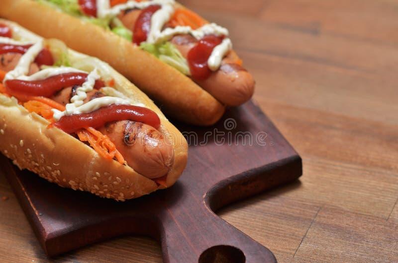 Hot dog z piec na grillu kiełbasą, czerwonym ketchupem, majonezem i warzywami, fotografia stock