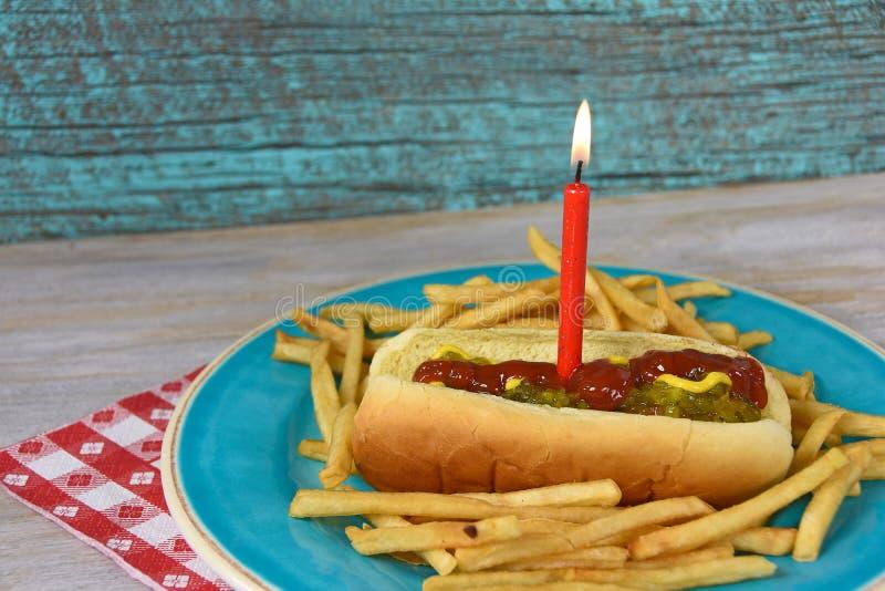 Hot dog z urodzinową świeczką i dłoniakami zdjęcia stock