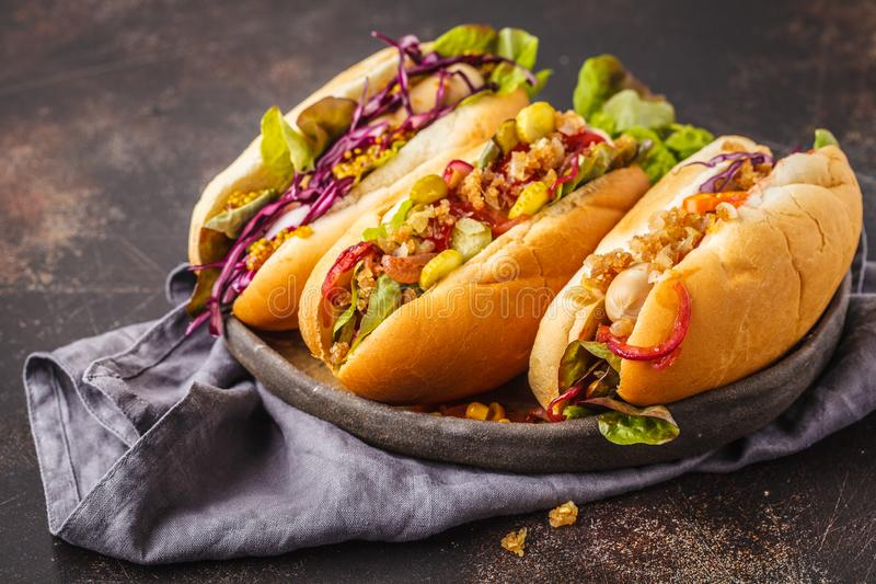 Hot dogs with assorted toppings on a dark background, top view royalty free stock photos