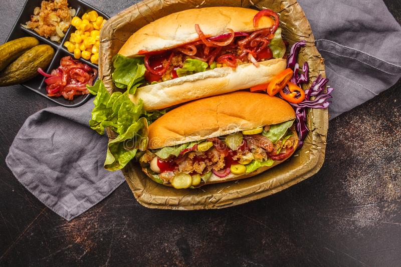 Hot dogs with assorted toppings on a dark background, top view stock image
