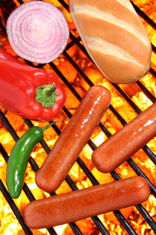 Hot dogs, bun and veggies on a barbecue grill. Hot dogs, bun and veggies on a fire hot barbecue grill. Barbecue & Outdoor Cooking Collection royalty free stock images