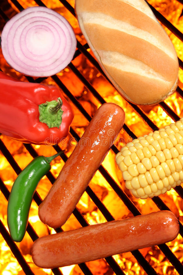Hot dogs, bun and veggies on a barbecue grill. Hot dogs, bun and veggies on a fire hot barbecue grill. Barbecue & Outdoor Cooking Collection stock images