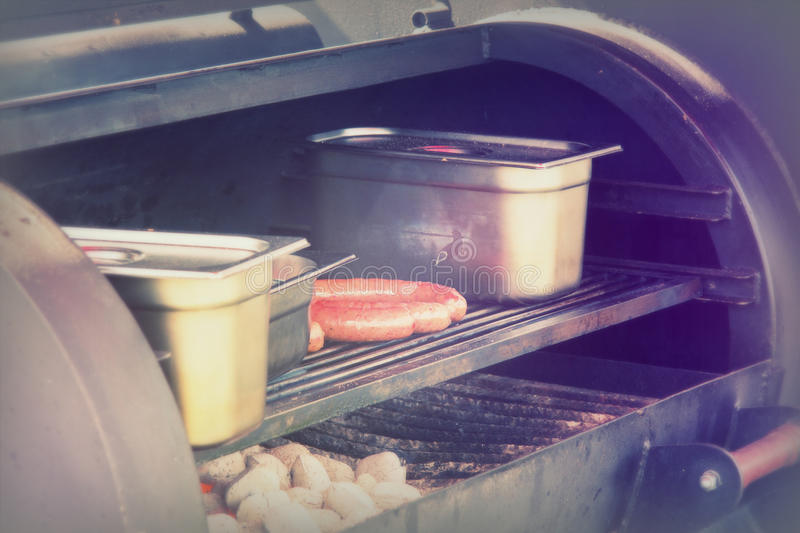 Hot dogs cooking on a bbq at market royalty free stock images