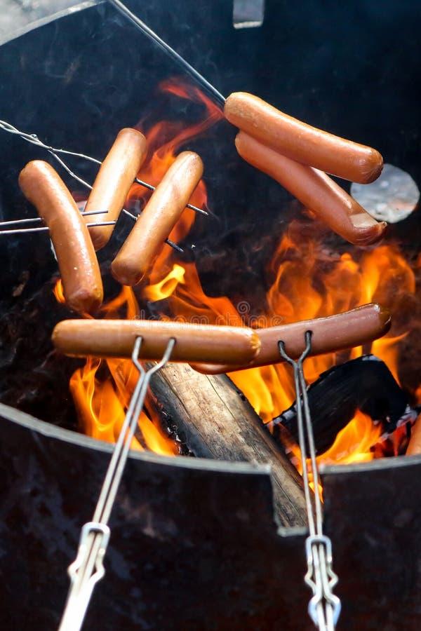Hot dogs de torréfaction au-dessus du feu image libre de droits