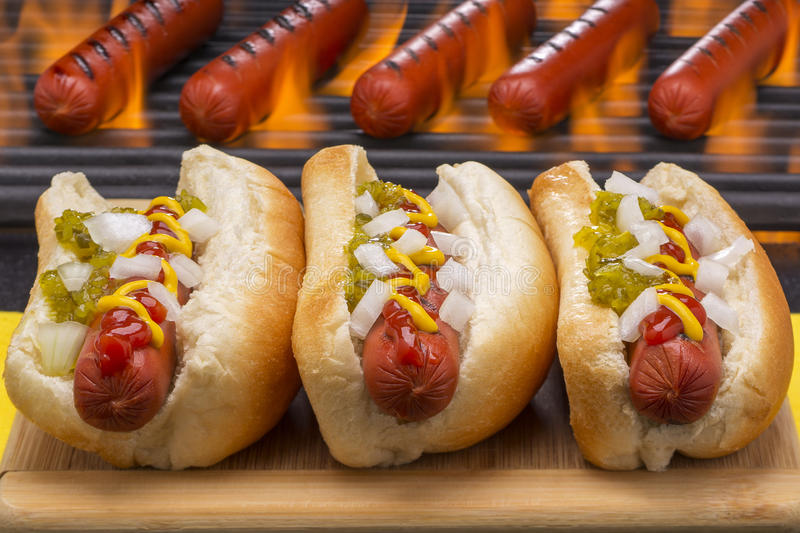 Hot Dogs Grilled in Buns Barbecue Grill Background. Three hot dogs with ketchup, onions, pickle relish and mustard in buns Grilled with a hot flaming barbecue royalty free stock images