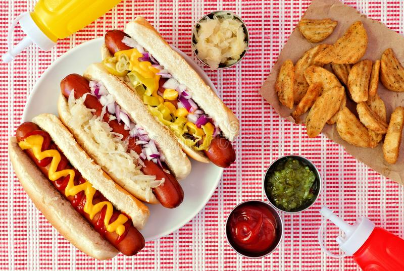 Hot dogs with potato wedges, above scene on checked cloth royalty free stock photos
