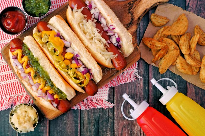 Hot dogs with potato wedges, above scene on rustic white wood stock image
