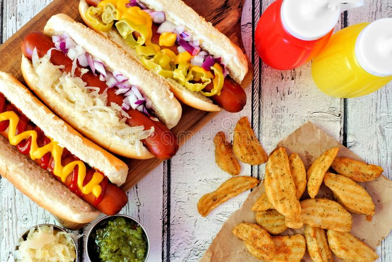 Hot dogs with potato wedges, above scene on rustic white wood royalty free stock photo