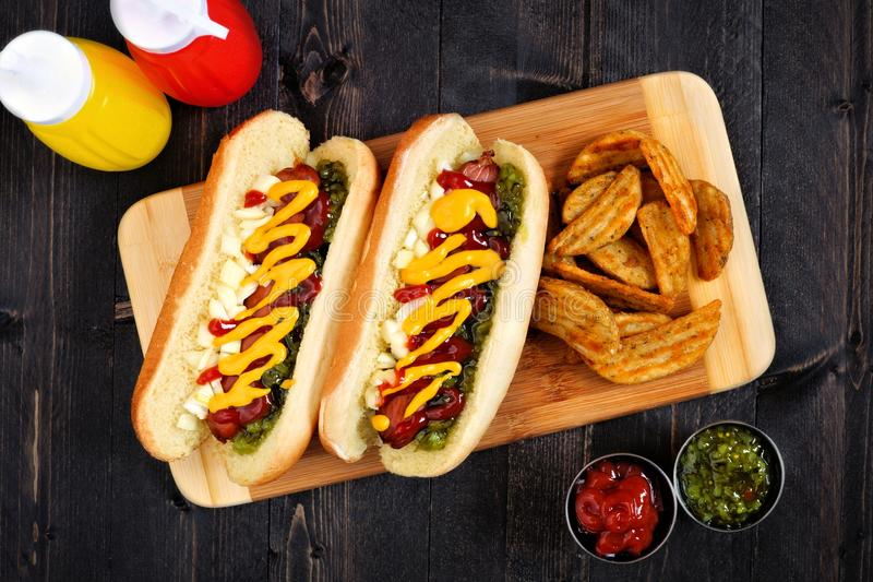 Hot dogs and potato wedges on wooden board, overhead scene. Two hot dogs fully loaded with toppings and potato wedges on wooden board, overhead scene royalty free stock image