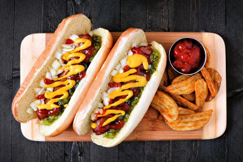 Hot dogs and potato wedges on wooden board, overhead view. Two hot dogs fully loaded with toppings and potato wedges on wooden board, overhead view royalty free stock images