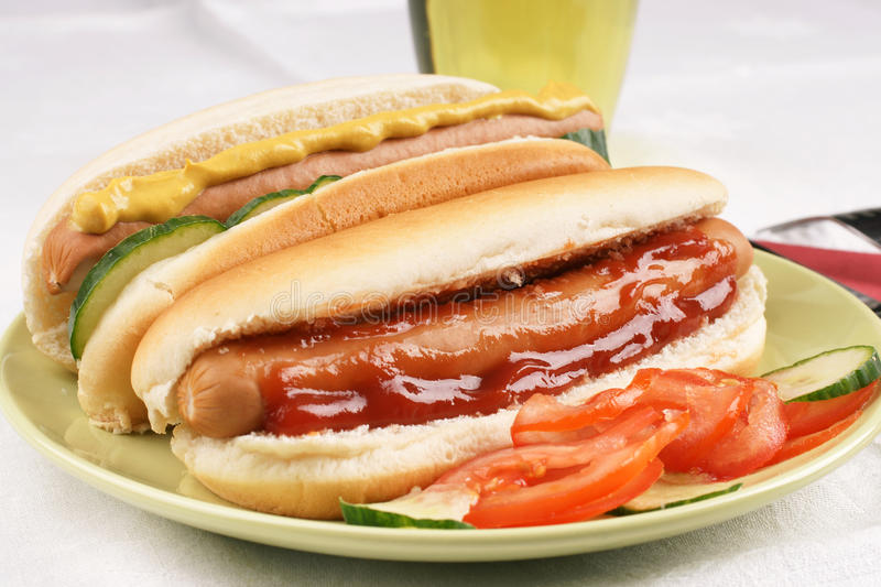 Hot Dogs with salad. Two hot dogs with ketchup and mustard and salad royalty free stock images
