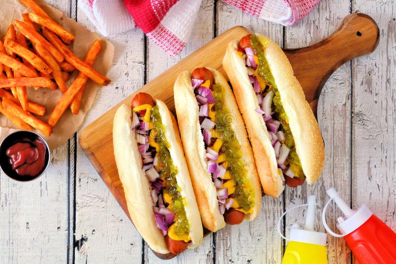 Hot dogs with onions, relish, mustard and ketchup served with french fries over white wood royalty free stock images