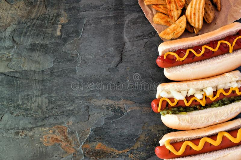 Hot dog side border, overhead view on a dark stone background. Hot dogs with toppings and potato wedges. Side border, top view on a dark stone background with royalty free stock photography