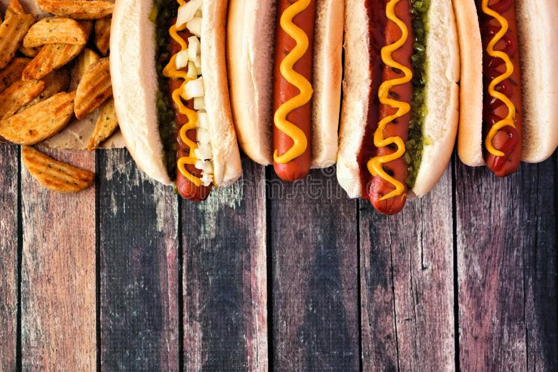 Hot dog top border, overhead view on a dark wood background. Hot dogs with toppings and potato wedges. Top border, above view on a dark wood background with copy stock photos