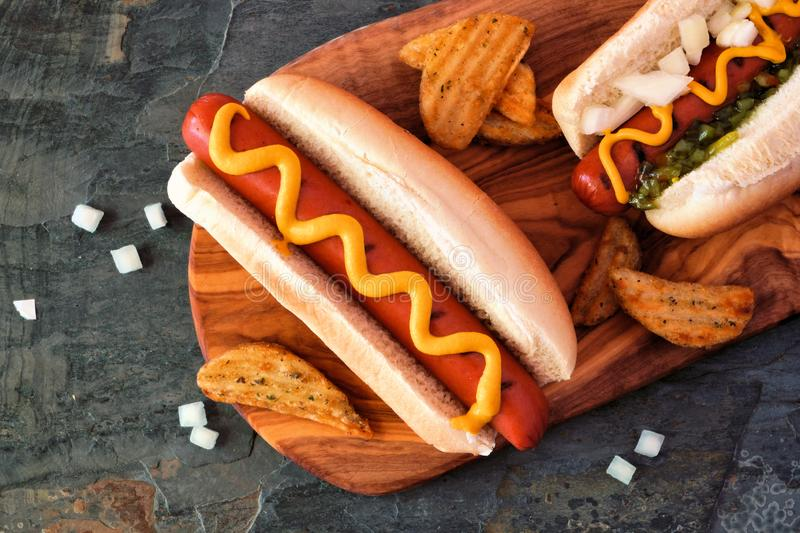Hot dogs and potato wedges on wooden board, close up, top view royalty free stock photography