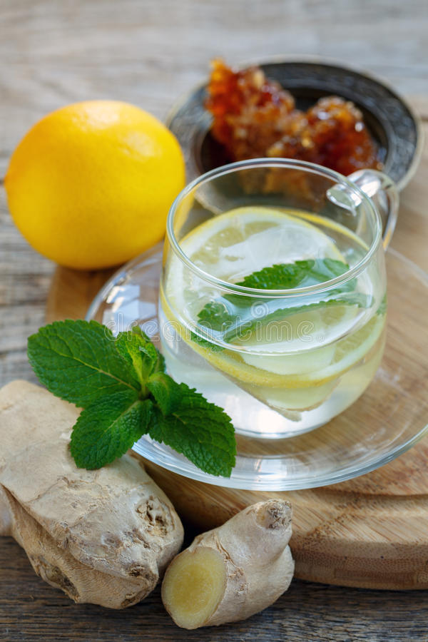 Hot drink with ginger, lemon, mint and honey. Hot drink with ginger, lemon, mint and honey in cup on a wooden table royalty free stock photography