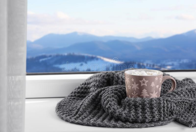 Hot drink and warm scarf near window with view of winter mountain. Landscape royalty free stock images