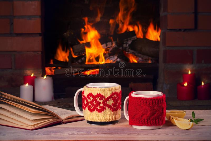 Hot drinks in mugs, book and candles on wooden table beside cosy open fire place. Autumn or winter holidays concept. Hot drinks in mugs, book and candles on royalty free stock photos