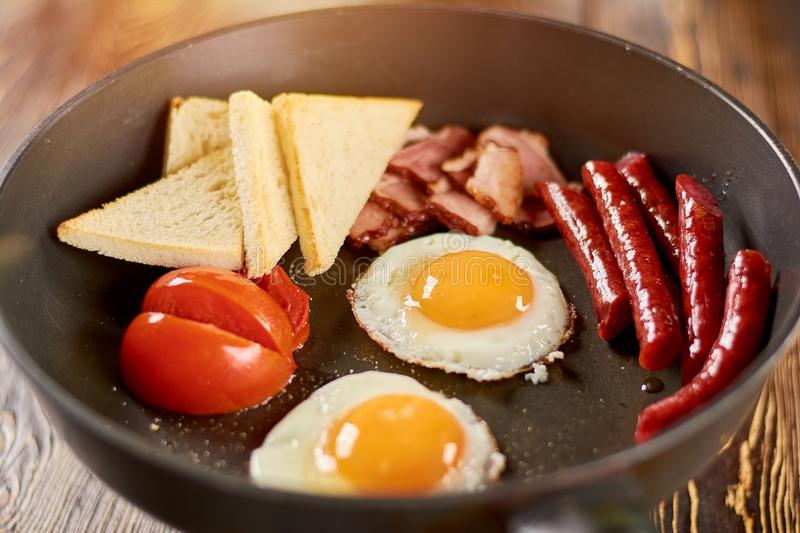 Hot english breakfast in skillet. Fried eggs with yolks, baked sausages and ham, toasts and tomatoes. Fresh english breakfast royalty free stock photo