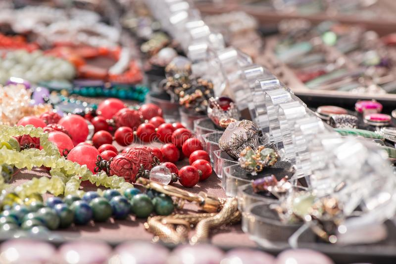 Hot of expensive gemstone jewelry. Rings, necklaces and bracelets made of peridot and azurite stones, red coral, sapphire, rose qu stock images