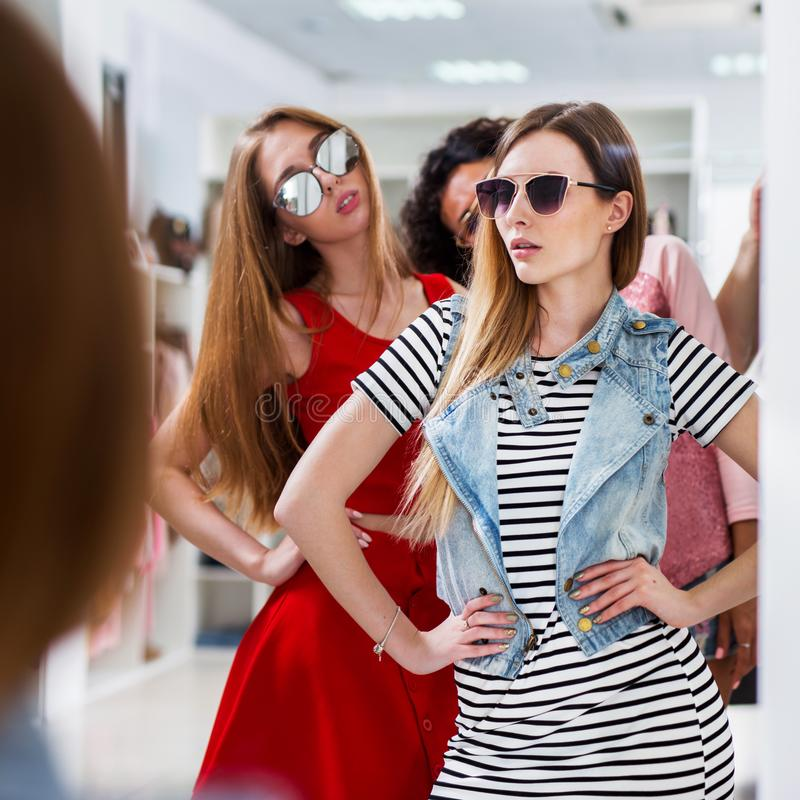 Hot fashionable young women wearing glasses posing looking in mirror standing in womenswear boutique.  royalty free stock image
