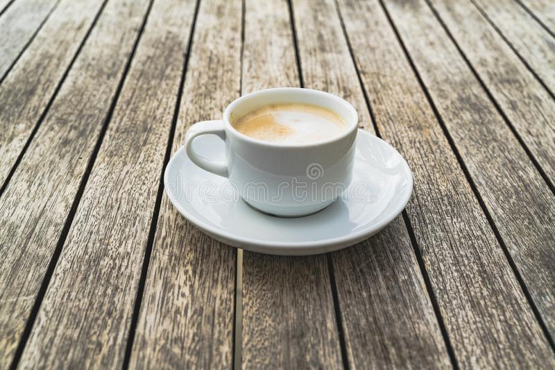 Hot foaming cappuccino in a white ceramic cup on a saucer stands on a table of wooden boards. Coffee is tasty drink and a good measure to feel good royalty free stock photo