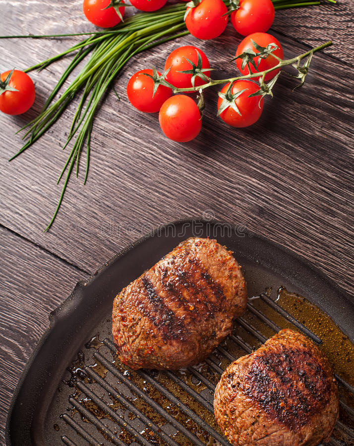 Hot fresh steaks on pan. With vegetables stock photos