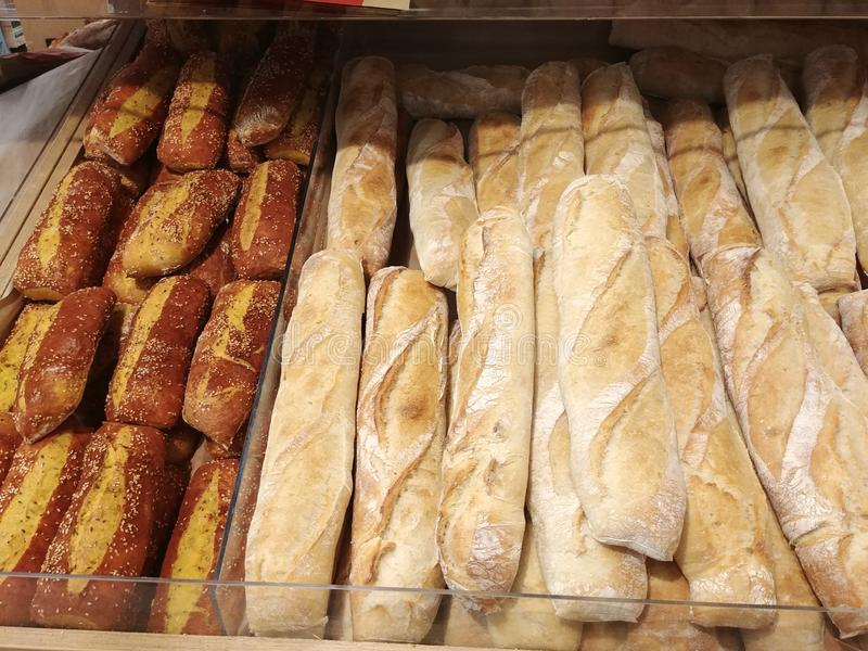 Hot freshly baked crisp french baguettes and fancy bread at storefront shelf royalty free stock images