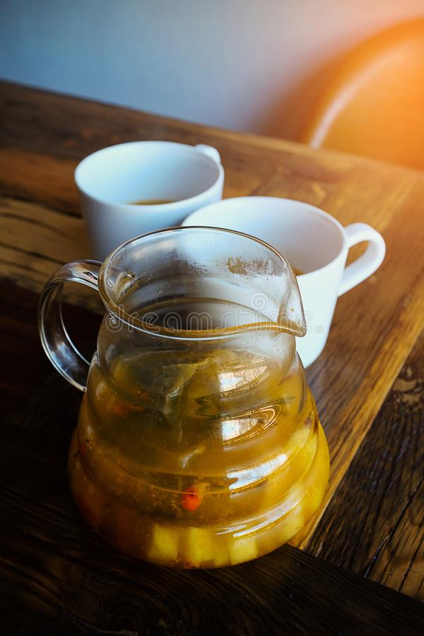 Hot fruit tea or hot lemonade. 2 mugs with tea. Delicious herbal tea with berries and leaves in a teapot on a wooden table. Warm royalty free stock photo