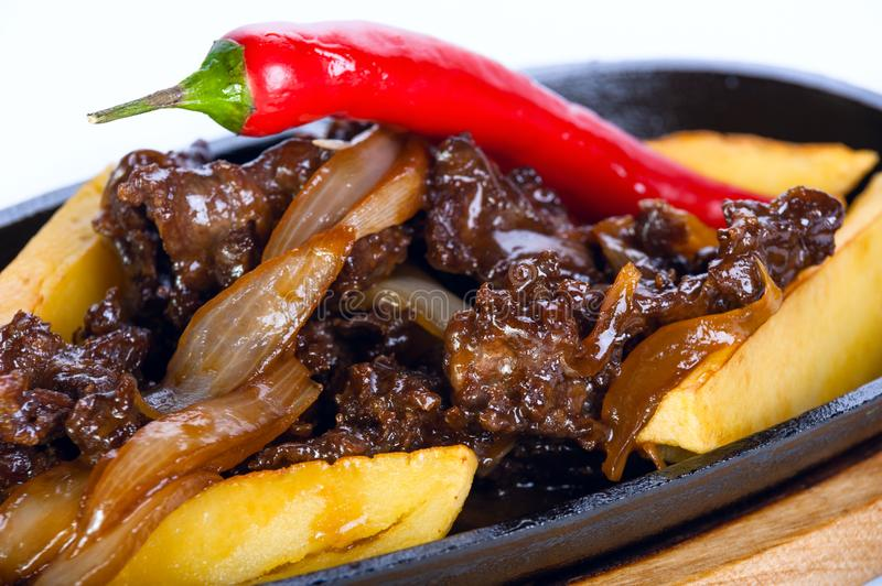 Hot frying pan. Roast meat with potatoes and red chili on a whit stock photo