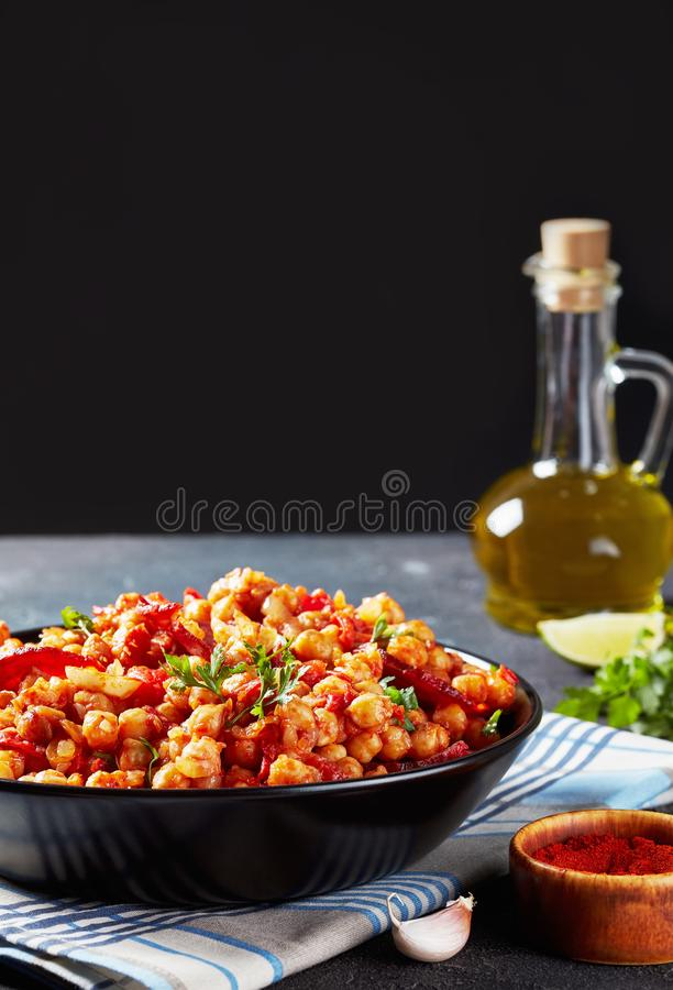 Hot Garbanzos fritos in a black bowl. Garbanzos fritos, hot Chickpea stew with sliced chorizo, ham, tomatoes and spices in a black bowl on a concrete table with stock images